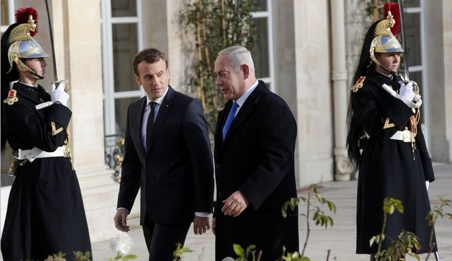 French President Emmanuel Macron, left, greets Israeli Prime Minister Benjamin Netanyahu before a meeting at the Elysee Palace in Paris, Sunday, Dec.10, 2017. Hundreds of pro-Palestinian protesters have demonstrated in Paris against the arrival of Israeli Prime Minister Benjamin Netanyahu saying his visit to meet French President Emmanuel Macron is not welcome, especially following this week's declaration by US President Donald Trump that Jerusalem is Israel's capital city. (AP Photo/Christophe Ena)