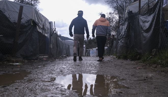 Migrants walk past makeshift tents outside the perimeter of the overcrowded Moria refugee camp on the northeastern Aegean island of Lesbos, Greece, Wednesday, March 11, 2020. Camps on Lesbos and other islands of the eastern Aegean are already overcrowded and operating above their capacity. (AP Photo/Aggelos Barai)