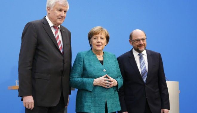 German Chancellor Angela Merkel, Chairwoman of the Christian Democratic Union, CDU, is flanked by Martin Schulz, chairman of the Social Democratic Party, SPD, and Bavarian Governor Horst Seehofer, chairman of the Christian Social Union, CSU, during a press statement after Merkel's conservatives and Germany's main center-left party reached a deal to form a new coalition government after a final session of talks that dragged on for 24 hours in the headquarters of the Christian Democratic Union in Berlin, Germany, Wednesday, Feb. 7, 2018. (AP Photo/Ferdinand Ostrop)