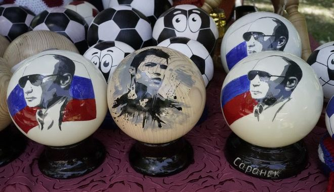 Hand made wooden balls depicting Russian president Vladimir Putin and soccer star Cristiano Ronaldo are offered for sale as souvenirs in Saransk, Russia, Sunday, June 17, 2018. Russia host the 2018 soccer World Cup. (AP Photo/Efrem Lukatsky)
