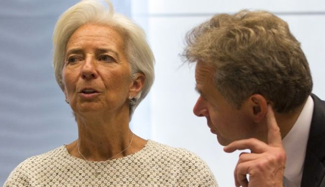 Managing Director of the International Monetary Fund Christine Lagarde, center, speaks with Director of the IMF's European Department Poul M. Thomsen during a meeting of eurozone finance ministers at the EU Lex building in Brussels on Saturday, July 11, 2015. Greece's negotiators head to Brussels on Saturday armed with their reform proposals and parliamentary backing to seek a third bailout, but with the shadow of severe dissent from governing lawmakers hanging over them. (AP Photo/Virginia Mayo)