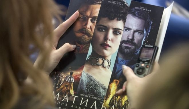 A woman hold an official poster of a Russian film director Alexei Uchitel's film Matilda at a news conference in Moscow, Russia, Tuesday, June 13, 2017. At the news conference Uchitel spoke about his latest film Matilda focused on Czar Nicholas II's romantic affair with ballet dancer Matilda Kshesinskaya. The film, which is to be released later this year, has aroused controversy in Russia. (AP Photo/Pavel Golovkin)