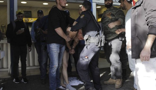 Israeli police officers hold a suspect at the scene of a stabbing attack in Jerusalem, Sunday, Dec. 10, 2017. (AP Photo/Sebastian Scheiner)