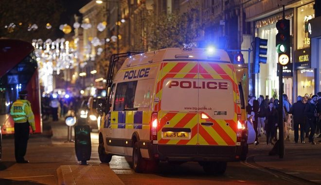 """Police officers and vehicles block Oxford Street in the west end of London after Oxford Circus station was evacuated Friday Nov. 24, 2017. British police flooded London's busy Oxford Circus area Friday after receiving multiple reports of """"shots fired."""" They have not located any casualties. (AP Photo/Alastair Grant)"""