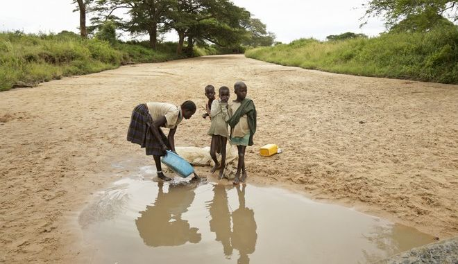 In this photo taken Wednesday, Oct. 18, 2017, a Karamojong woman washes clothes at a small pool of water in a dried-up riverbed in the semi-arid savannah region of Karamoja, in northeastern Uganda. As international leaders meet in Germany for the first major global climate conference since President Donald Trump announced that the U.S. will pull out of the 2015 Paris accord, many in Africa fear they will be harder-hit than most and in Uganda's poorest region Karamoja, the changing climate has brought hunger and bewilderment as traditional coping methods fail. (AP Photo/Adelle Kalakouti)