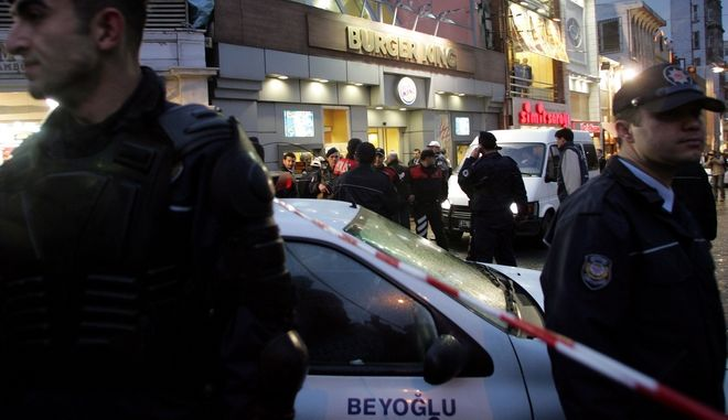 """Turkish policemen cordon off area around a popular fast food restaurant in down town Istanbul, Turkey, Saturday, April 8, 2006. Two men wearing T-shirts with """"Turkey"""" written on them took a hostage at a popular Burger King restaurant and then released him after negotiations with police. Istanbul Chief of Police Celalettin Cerrah said both hostage-takers were soldiers who were absent without leave. Cerrah said they were protesting clashes between Kurds and security forces in the southeast and that the guns they brandished were blank-firing guns. (AP Photo/Murad Sezer)"""
