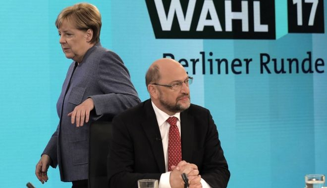 German Chancellor Angela Merkel, head of the Christian Democratic Party CDU, passes by her challenger Martin Schulz, head of the Social Democratic Party SPD, prior to a TV talk of the party leader in Berlin, Germany, Sunday, Sept. 24, 2017, after the German parliament elections. (AP Photo/Gero Breloer, pool)