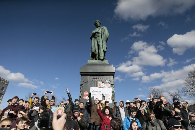 People surround Alexander Pushkin monument with a poster reading: Dimon ( Prime Minister Dmitry Medvedev) Give Money Back, in downtown Moscow, Russia, Sunday, March 26, 2017. Russia's leading opposition figure Alexei Navalny and his supporters aim to hold anti-corruption demonstrations throughout Russia. But authorities are denying permission and police have warned they won't be responsible for