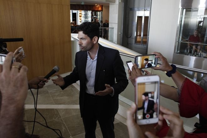 Orestes Fintiklis, manager of the Miami-based private equity fund Ithaca Capital, talks to the press in the lobby of the Trump Ocean Club International Hotel and Tower in Panama City, Monday, March 5, 2018. Escorted by police officers and a Panamanian judicial official, the owner of the Trump Panama City hotel has taken control of the property. A team of Trump security officials left the property. (AP Photo/Arnulfo Franco)