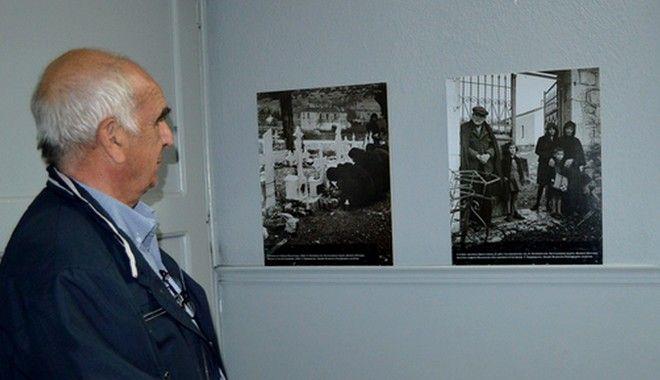Ο Θανάσης Πανουργιάς κοιτάζει τις φωτογραφίες με τους μαυροντυμένους ανθρώπους που βρίσκονται στο Μουσείο. Αριστερά, γυναίκες ανάβουν τα καντήλια στους τάφους. Δεξιά, ο Τάκης Σφουντούρης, γνωστός και ως