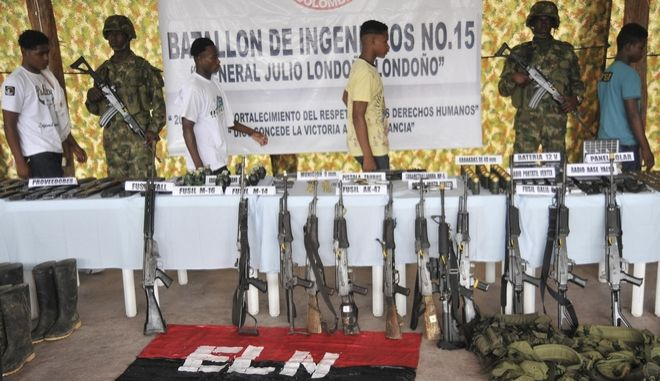 Demobilized rebels walk behind weapons they surrendered at a military base in Tarido, Colombia, Sunday, Dec.7, 2008. About seventeen rebels of the National Liberation Army, ELN, Colombia's second largest group, surrendered to the army with their weapons. (Luis Benavides)