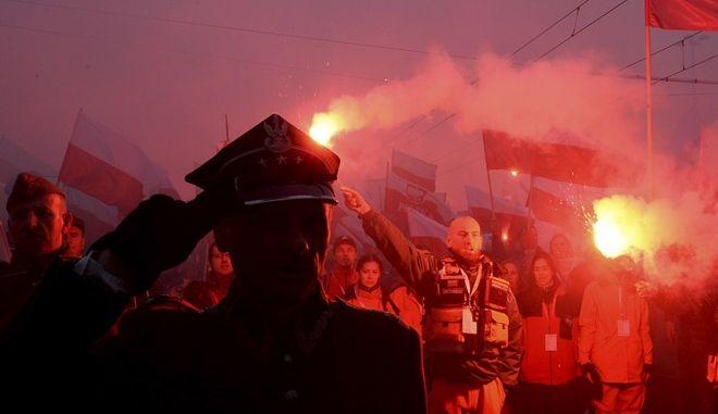 Διαδηλωτές με φωτοβολίδες κατά τη διάρκεια της πορείας για την Ημέρα της Ανεξαρτησίας