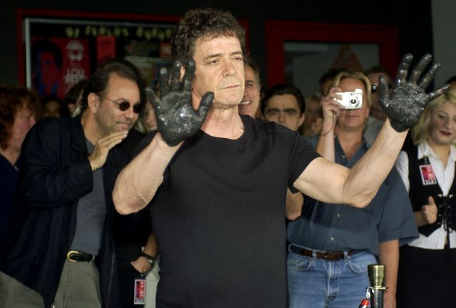 Music icon Lou Reed displays his muddy hands with actor/musician Ruben Blades, left, and other supporters cheering in the background Tuesday, June 24, 2003, in the Hollywood section of Los Angeles. Reed was inducted into Hollywood's Rockwalk. (AP Photo/Ric Francis)