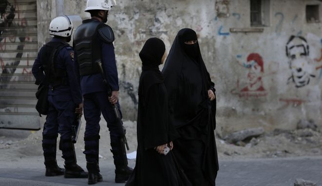 Bahraini women pass by riot police watching for protesters, to prevent a third day gathering of demonstrators against Saudi Arabia's execution of Shiite cleric Sheikh Nimr al-Nimr in Daih, Bahrain, a largely Shiite suburb of the capital, Monday, Jan. 4, 2016. Graffiti on the wall is of people killed in previous unrest. Allies of Saudi Arabia, including the monarchy in neighboring Bahrain, began scaling down their diplomatic ties to Iran in the wake of the ransacking of Saudi diplomatic missions in Iran that followed al-Nimr's execution. (AP Photo/Hasan Jamali)