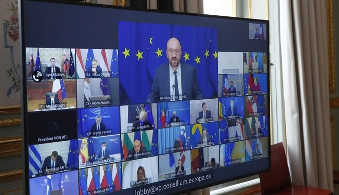 European Council President Charles Michel shown on a screen, center, speaks during a video conference of a EU summit at the Elysee Palace in Paris, Thursday March 25, 2021. The looming third wave of coronavirus infections and Europe's struggle to mount a vaccination drive will dominate Thursday's EU video summit. (AP Photo/Michel Euler, Pool)