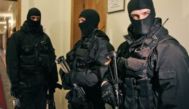 Ukrainian national security service armed agents wearing masks raid the headquarters of the country's natural gas company, Naftogaz, in Kiev, Ukraine, Wednesday, March 4, 2009. The raid by armed agents was in connection with a criminal investigation launched this week into the alleged diversion of gas worth around 7.4 billion hryvna ($900 million), SBU national security service spokeswoman Marina Ostapenko told The Associated Press. (AP Photo/Efrem Lukatsky)