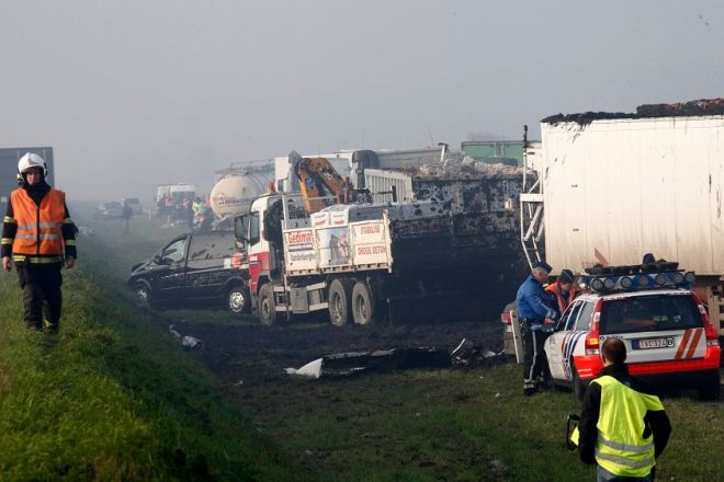 Belgian police officers and firefighters gather at the scene of a pileup involving dozens of cars and trucks near Zonnebeke, Belgium, Tuesday, Dec. 3, 2013. Dozens of vehicles crashed in dense morning fog in western Belgium, killing at least two people and injuring dozens more. (AP Photo / Michel Spingler)