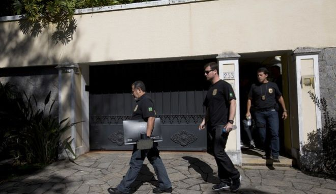 A Federal Police officer carries a flat screen confiscated from the home of Carlos Nuzman, president of the Brazilian Olympic committee, Tuesday, Sept. 5, 2017, in Rio de Janeiro, Brazil. Federal police searched Nuzman's house Tuesday morning. French and Brazilian authorities have been working on a corruption investigation involving bribery surrounding the awarding of the 2016 Rio Games and the 2020 Tokyo Games. (AP Photo/Silvia Izquierdo)