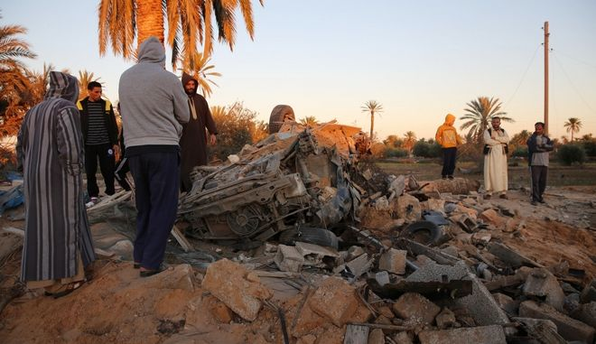 In this Friday, Feb. 19, 2016 photo, people gather after an air strike on a house and training camp belonging to the Islamic State group, west of Sabratha, Libya. American F-15E fighter-bombers struck an Islamic State militant training camp in rural Libya near the Tunisian border Friday, killing dozens, probably including an IS operative considered responsible for deadly attacks in Tunisia last year, U.S. and local officials said. (AP Photo/Mohamed Ben Khalifa)