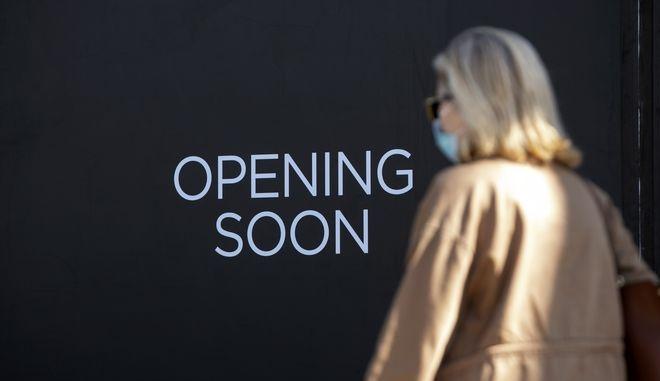 Γυναίκα με μάσκα μπροστά σε κλειστό κατάστημα στην Αθήνα