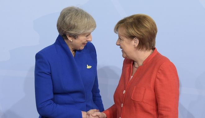 British Prime Minister Theresa May, left, is welcomed by German Chancellor Angela Merkel on the first day of the G-20 summit in Hamburg, northern Germany, Friday, July 7, 2017. The leaders of the group of 20 meet July 7 and 8. (AP Photo/Jens Meyer)