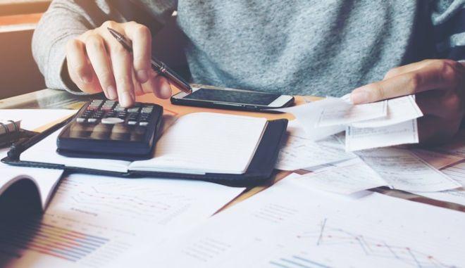 Ένας άντρας υπολογίζει τις φορολογικές του υποχρεώσεις