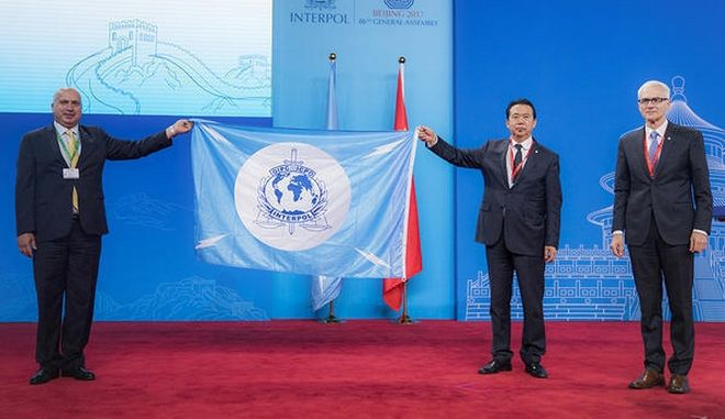 CAPTION CORRECTS FLAG  TO INTERPOL FLAG In this photo provided by Interpol, a Palestinian delegate receives the INTERPOL flag from the president of the International Criminal Police Organization Meng Hongwei second right, during the Interpol General Assembly, in Beijing, China, Wednesday, Sept. 27, 2017.  International police agency Interpol voted Wednesday to include the Palestinian state as a member state, in a new boost to Palestinian efforts for international recognition and influence amid long-stalled negotiations with Israel for full statehood. (Interpol via AP)