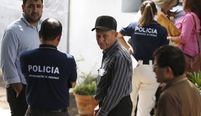 Abraham Fehr, center, the father of a Mexican farmer kidnapped for ransom three years, talks with police after receiving confirmation that a body recovered in northern Paraguay is that of his son, in Asuncion, Paraguay, Friday, Jan. 12, 2018. A member of a Mennonite colony, 36-year-old Abraham Fehr was kidnapped on Aug. 8, 2015. The Paraguayan People's Army then requested a ransom of $ 500,000 but the father maintained that they did not have that sum of money. Fehr's body was found inside in a grave on Thursday. (AP Photo/Jorge Saenz)