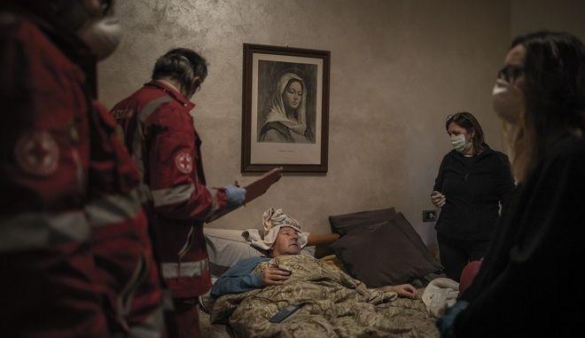 Ο Claudio Travelli (61), ασθενής με Covid-19, αναπαύεται στο κρεβάτι του μετά από την εξέταση από τους εθελοντές του Διεθνούς Ερυθρού Σταυρού, 15 Μαρτίου 2020, στο Κάτω Τσενάτε στο Μπέργκαμο της Ιταλίας. Μετά την εξέτασή του ο Travelli αποφασίζει να παραμείνει σπίτι. Την επόμενη μέρα η οικογένειά του αποφασίζει να καλέσει ασθενοφόρο επειδή η κατάστασή του χειροτερεύει. Ο Claudio εισήχθη στο νοσοκομείο και παρέμεινε στην ΜΕΘ και ΜΑΦ για τρεις εβδομάδες και πήρε εξιτήριο στις 3 Απριλίου.