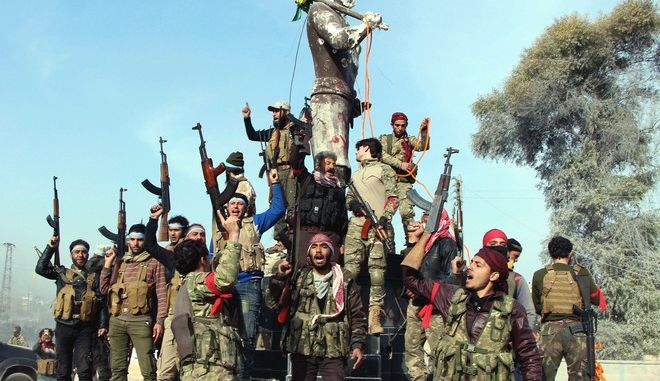 """Turkey-backed Free Syrian Army soldiers celebrate around a statue of Kawa, a mythology figure in Kurdish culture as they prepare to destroy it in city center of Afrin, northwestern Syria, early Sunday, March 18, 2018. Turkey's President Recep Tayyip Erdogan said Sunday that allied Syrian forces have taken """"total"""" control of the town center of Afrin, the target of a nearly two-month-old Turkish offensive against a Syrian Kurdish militia, which said fighting was still underway. Erdogan said the Turkish flag and the flag of the Syrian opposition fighters have been raised in the town, previously controlled by the Kurdish militia known as the People's Defense Units, or YPG. (Hasan Krmzita/DHA-Depo Photos via AP)"""