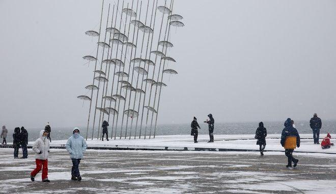 Πολίτες περπατούν στη χιονισμένη Νέα Παραλία Θεσσαλονίκης