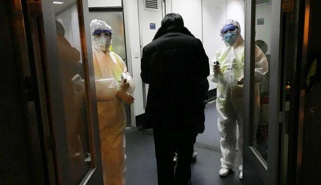 Οι υπάλληλοι της υγειονομικής περίθαλψης περιμένουν στην πύλη για να ελέγξουν τις θερμοκρασίες σώματος των επιβατών που φθάνουν από την πόλη του Wuhan