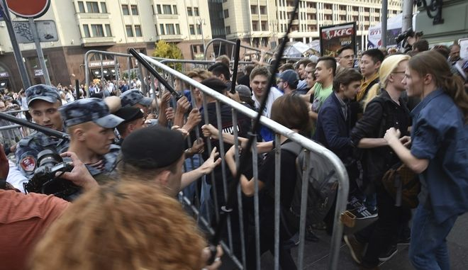 Police try to block protesters during rally protesting retirement age hikes in Moscow, Russia, Sunday, Sept. 9, 2018. A government plan to increase the age for collecting state pensions brought protests across Russia's 11 time zones on Sunday even though the opposition leader who called them was in jail. Nearly 300 people were reported arrested. (AP Photo/Dmitry Serebryakov)