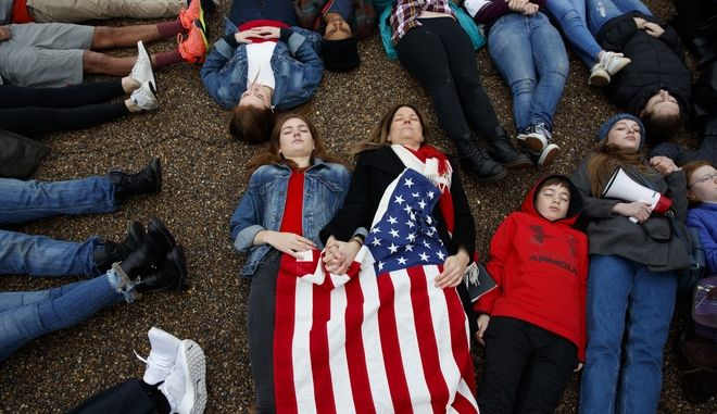 "Abby Spangler and her daughter Eleanor Spangler Neuchterlein, 16, hold hands as they participate in a ""lie-in"" during a protest in favor of gun control reform in front of the White House, Monday, Feb. 19, 2018, in Washington. (AP Photo/Evan Vucci)"