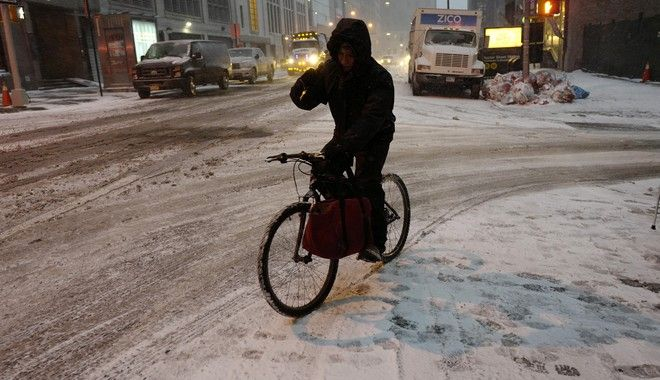 A bicyclist maneuvers through an early morning snowfall, Thursday, Jan. 4, 2018, in New York. Residents across a huge swath of the U.S. awakened Thursday to the beginnings of a massive winter storm expected to deliver snow, ice and high winds followed by possible record-breaking cold as it moves up the Eastern Seaboard from the Carolinas to Maine. (AP Photo/Mark Lennihan)