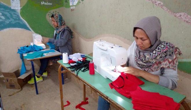 Αφγανές φτιάχνουν μάσκες για τους πρόσφυγες.