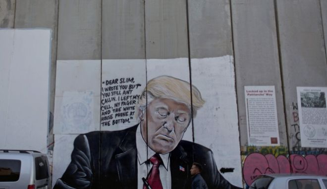 A Palestinian man walks past a section of Israel's West Bank separation barrier with a mural that depicts President Donald Trump, in the West Bank city of Bethlehem, Sunday, Dec. 3, 2017. (AP Photo/Nasser Nasser)