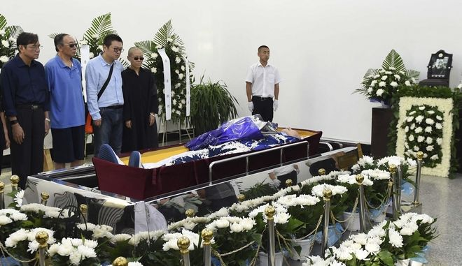 In this photo provided by the Shenyang Municipal Information Office, relatives stand next to the casket of jailed Nobel Peace Prize winner and Chinese dissident Liu Xiaobo during his funeral at a funeral parlor in Shenyang in northeastern China's Liaoning Province, Saturday, July 15, 2017. From left Liu Xiaoxuan, younger brother of Liu Xiaobo, Liu Xiaoguang, older brother of Liu Xiaobo, Liu Hui, younger brother of Liu Xia, and Liu Xia. (Shenyang Municipal Information Office via AP)