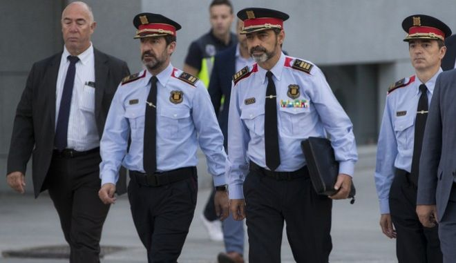 Catalan regional police chief Josep Luis Trapero, 3rd left, arrives at the national court in Madrid, Spain, Friday, Oct. 6, 2017. A Spanish judge is due to question Mossos d'Esquadra chief Trapero and two pro-independence campaigners about their role in an Oct. 1 referendum that the Spanish government declared as illegal. (AP Photo/Paul White)
