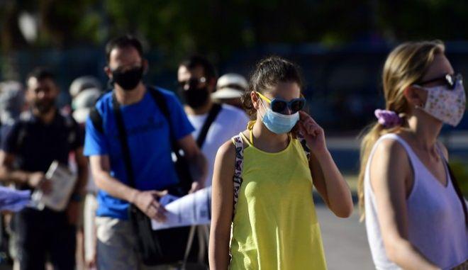 Άνθρωποι με μάσκα στο λιμάνι του Πειραιά