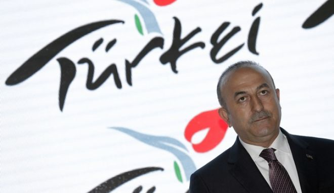 The Foreign Minister of Turkey Mevlut Cavusoglu visits the booth of Turkey at the tourism fair ITB in Berlin, Germany, Wednesday, March 8, 2017. (AP Photo/Michael Sohn)