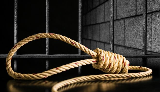 Brown rope noose dark and light on black table with old prison bars cell lock background dark black and light, concept of punishment