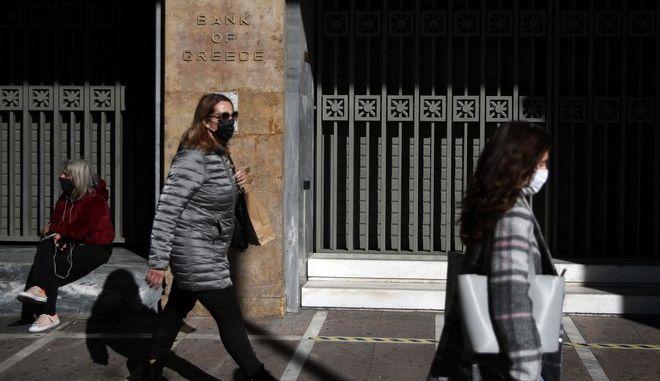 Γυναίκα με μάσκα περνάει έξω από την τράπεζα της Ελλάδος