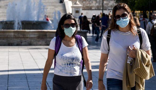 Κόσμος με μάσκες περπατά στο Σύνταγμα