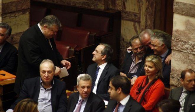 Ο πρωθυπουργός Αντ. Σαμαράς συνομιλεί με τον πρόεδρο του ΠΑΣΟΚ, Ευαγ. Βενιζέλο  στην συζήτηση για τους πλειστηριασμούς στην Ολομέλεια της Βουλής το Σάββατο 21 Δεκεμβρίου 2013. (EUROKINISSI/ΓΙΩΡΓΟΣ ΚΟΝΤΑΡΙΝΗΣ)