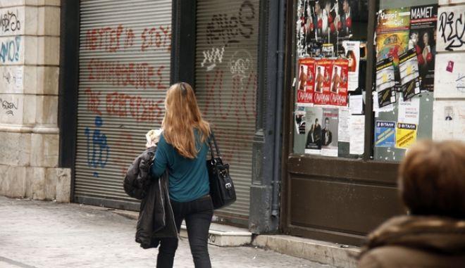 Κόσμος περνά έξω από κλειστό εμπορικό κατάστημα στην Αθήνα την Τετάρτη 15 Ιανουαρίου 2014. (EUROKINISSI/ΓΙΩΡΓΟΣ ΚΟΝΤΑΡΙΝΗΣ)