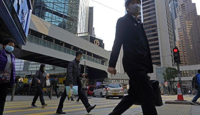 Διερχόμενοι με μάσκες λόγω κοροναϊού σε κεντρικό δρόμο του Χονγκ Κονγκ