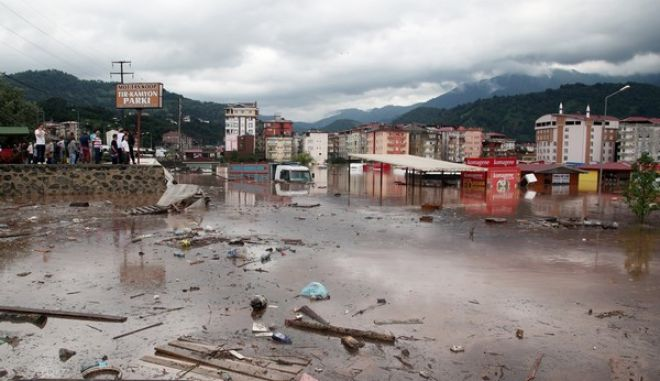 People look at a flooded street in Artvin, near Turkeys border with Georgia, Monday, Aug. 24, 2015. Officials say at least eight people have been killed in northeast Turkey from heavy floods and a landslide triggered by torrential rains. Three of the victims were trapped inside a house which collapsed in the town of Hopa, on Turkeys Black Sea coast, according to a statement from the Artvin governors office.(IHA via AP) TURKEY OUT