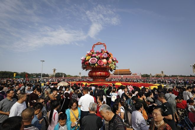 Visitors gather near a giant basket decorated with replicas of flowers and fruits on display at Tiananmen Square on China's National Day in Beijing, Sunday, Oct. 1, 2017. Hundreds of thousands foreign and domestic tourists flock to the square to celebrate the 68th National Day and the Mid-Autumn Festival over the week-long holidays. (AP Photo/Andy Wong)