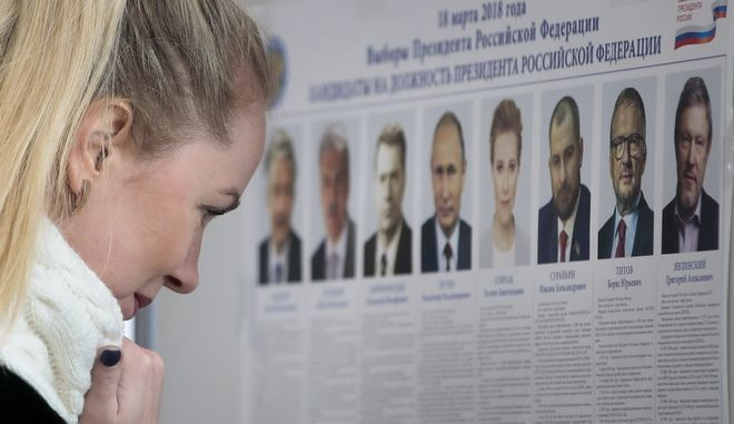 A woman reads a list of candidates for the 2018 Russian presidential election at the polling station, in Moscow, Sunday, March 18, 2018. Russians are voting in a presidential election in which Vladimir Putin is seeking a fourth term in the Kremlin. (AP Photo/Denis Tyrin)